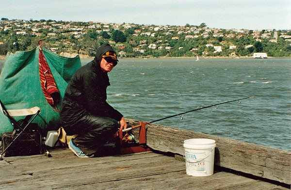 Weighting for a bite. Salmon fishing from the wharves in Otago Harbour.