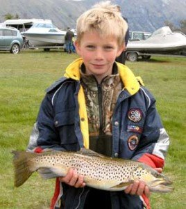 This young angler has caught a fine looking butter coloured brown trout.
