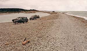 In this picture taken on the south side of the Rangitata River mouth the angling owners of these 4WD vehicles have wisely parked up and walked the rest of the way to the mouth proper. The very narrow spit with its loose gray wacke stones is too unstable for these heavy vehicles.