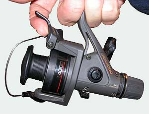 The Shimano AX Spinning Reel. The QuickFire II lever is shown in use. It always stops at the top when you wind the handle backwards.