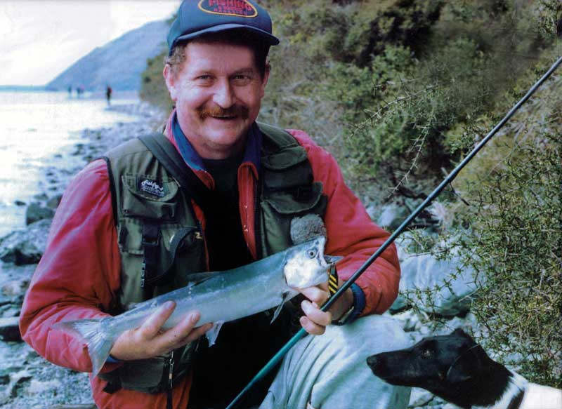 Allan Burgess with a landlocked salmon taken spin fishing at the Picket Fence, Lake Coleridge, 1996. The curious dog wasn't mine. He just likes fish!