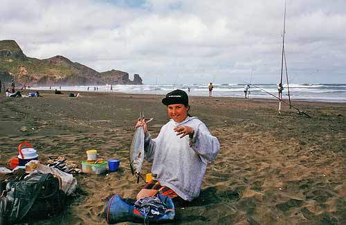 """Clair MacDowall and her """"just caught"""" kahawai on Bethells Beach. In this view, we are looking south down Bethells Beach. The waves from the two-metre swell are visible in the background. Bethells and O'Neils Beaches Surfcasting Contest."""