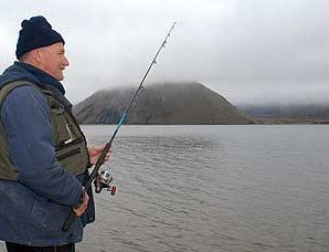 Spin fishing around the shoreline of Lake Heron. In the back ground Mt Sugarloaf is shrouded by low cloud.