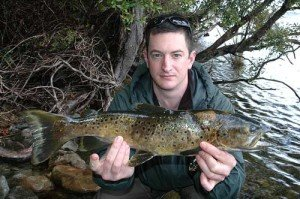 Lake Brunner trout fishing: Dan Sweeny with a dark coloured brown trout taken at Lake Brunner while fishing with local guide Brent Beadle. Note the typical colouration of fish from Westland lakes.