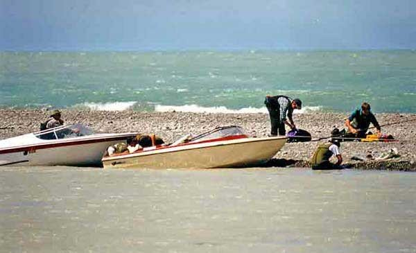 Salmon anglers clean their catch on a shingle bar at the mouth of the Waitaki River. The Waitaki is a big river often flowing at 500 cumecs or more. Access to the best salmon fishing is improved enormously with a jet boat. However they do take knowledge, skill and experience to handle safely. Almost every year at least one jet boat is lost to the river.