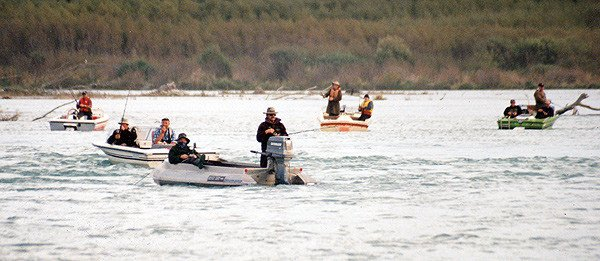 Salmon anglers fishing from jet boats on the lower Waitaki River.