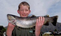 This young angler looks pleased with his big brown trout.