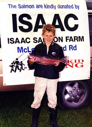 David Marshall (aged 13) with a rainbow trout he caught at the Groynes Take A Kid Fishing Day.. Note the sign, the late Lady Isaac was a staunch supporter of TAKF.