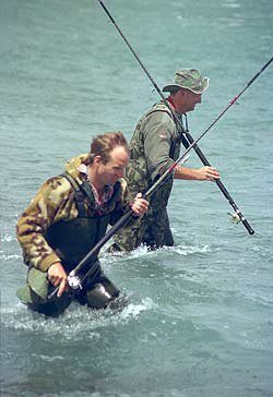 Salmon anglers at the Rakaia River mouth with low-mount surf rods.