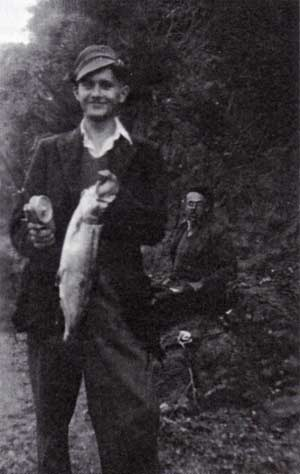 The author is delighted with this rainbow trout caught back in 1951. Charlie is in the background.