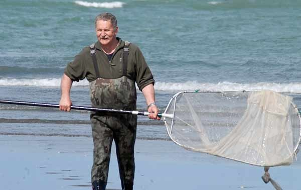 The author with his trusty pole net at the mouth of the Waimakariri River.