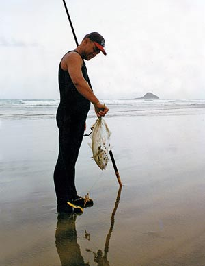 A contestant with a trevally caught on tuatua bait. Motupia lsland is in the background.