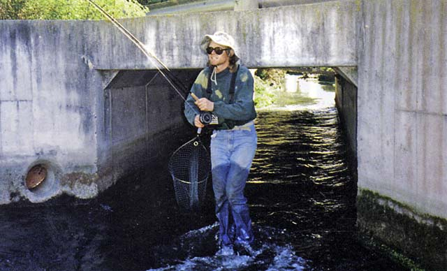 Greg reappears from the concrete culvert under the road with his trout. Small stream fishing.