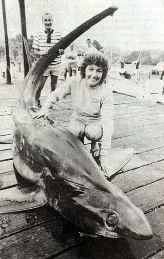 """The flat snout, huge eyes and the hump in the back immediately behind the eyes identifies this shark as a bigeye thresher (Alopias superciliosus). The shark weighed 363.80 kg (802 lb) and is the current l.G.F.A. All Tackle World Record. The smiling lady angler is Mrs Dianne North and holding the thresher's tail is Garth Marsland, skipper of successful game boat """"Maestro."""" Photo by courtesy of the Northern Advocate."""
