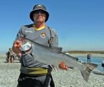 man holding bright silver salmon caught in the Rakaia River Gut in 2015.