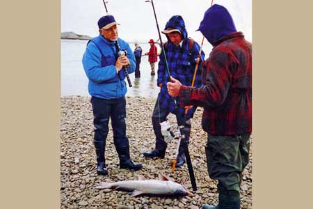 Three anglers examine a salmon catch. The Hunt for Houdini.