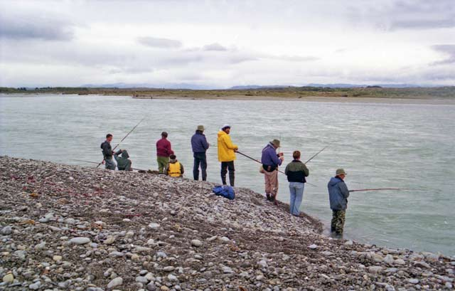 Salmon fishers casting at the wide Waitaki River gut.