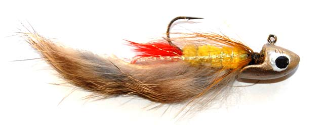 "A Yellow Rabbit streamer pattern tied on a 1/4 oz jig head. This ""lure"" will cast a long way and sink quickly when cast on spinning gear and braided line."