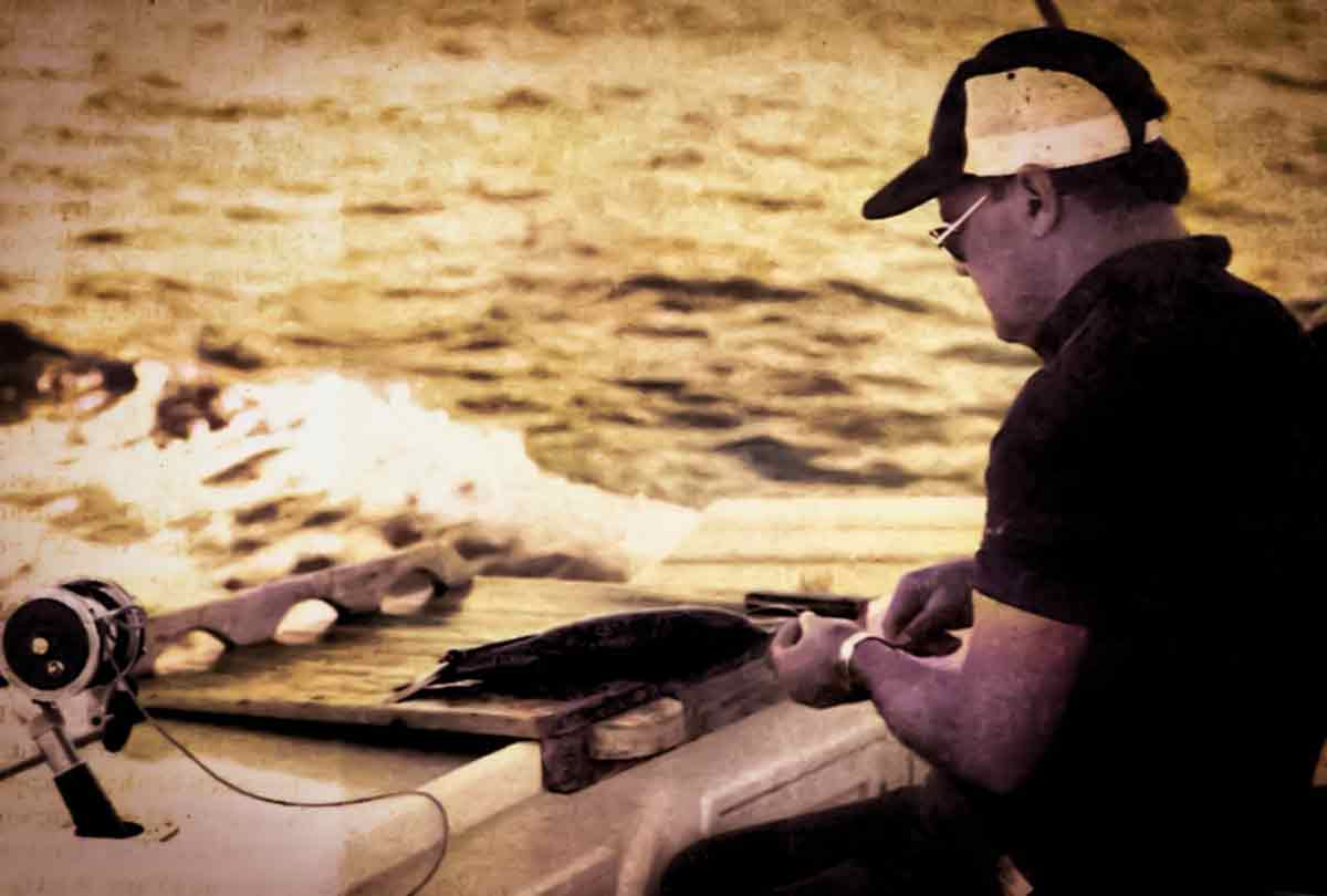 "Displaying the skills of a surgeon, Skipper David Auld rigs a kahawai ""skip bait."