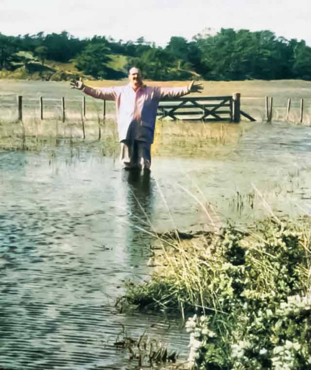 The track through the farm is usually dry. The author stands in a paddock after heavy rain.