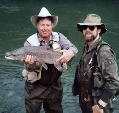 A younger looking Tony Entwistle (right), with client John Hewitt from the United States of America, holding for the camera one of four 10lb plus trout caught and released in a single afternoon in the Nelson region. Hiring a trout fishing guide. Now retired, Tony is a Life Member and former President of the NZPFGA.
